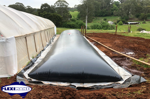 water storage bladder tank installed next to a greenhouse