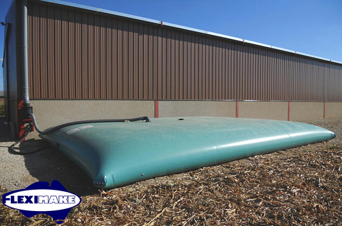 Rain water collecting flexible bladder tank install next to a warehouse building with piping connections
